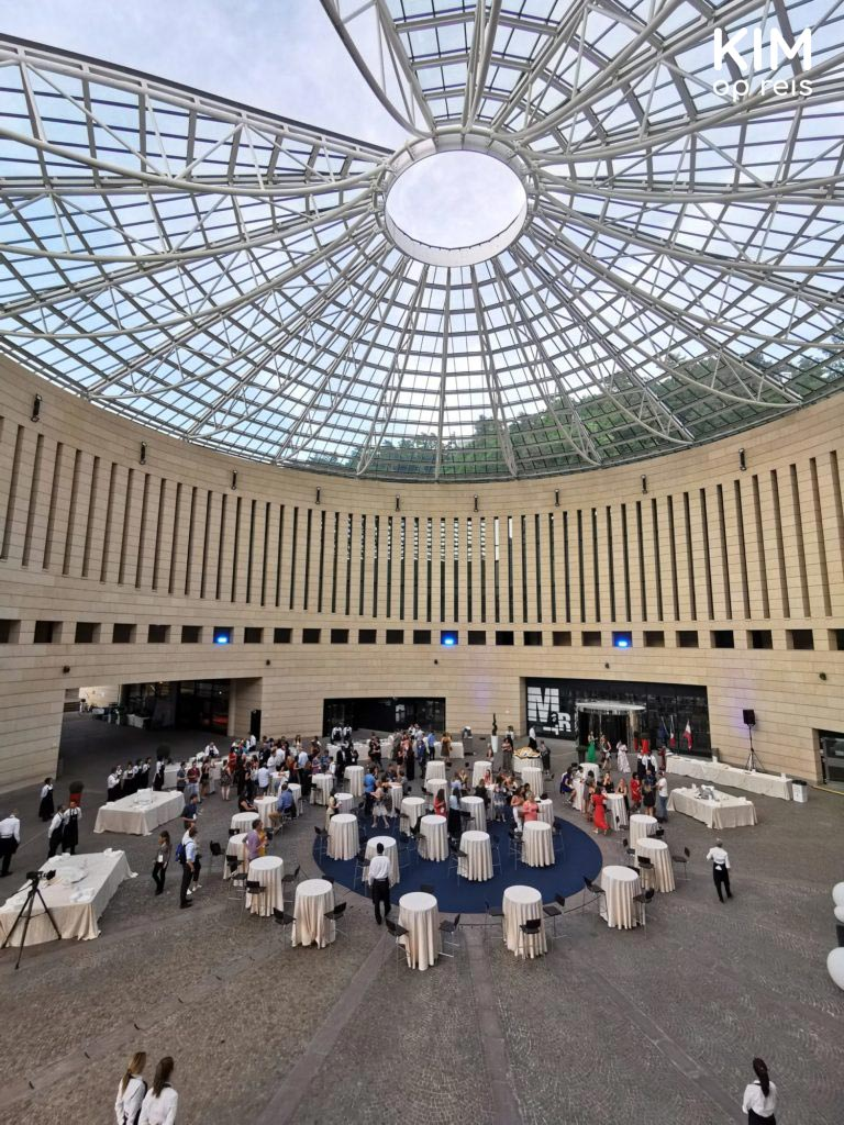 Event in MART museum - high, round space with a glass roof and people around standing tables