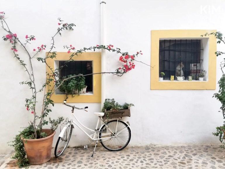 Fietstour Ibiza-stad - wit huis met gele raampjes en een grote plant met roze bloemen en een fiets ervoor