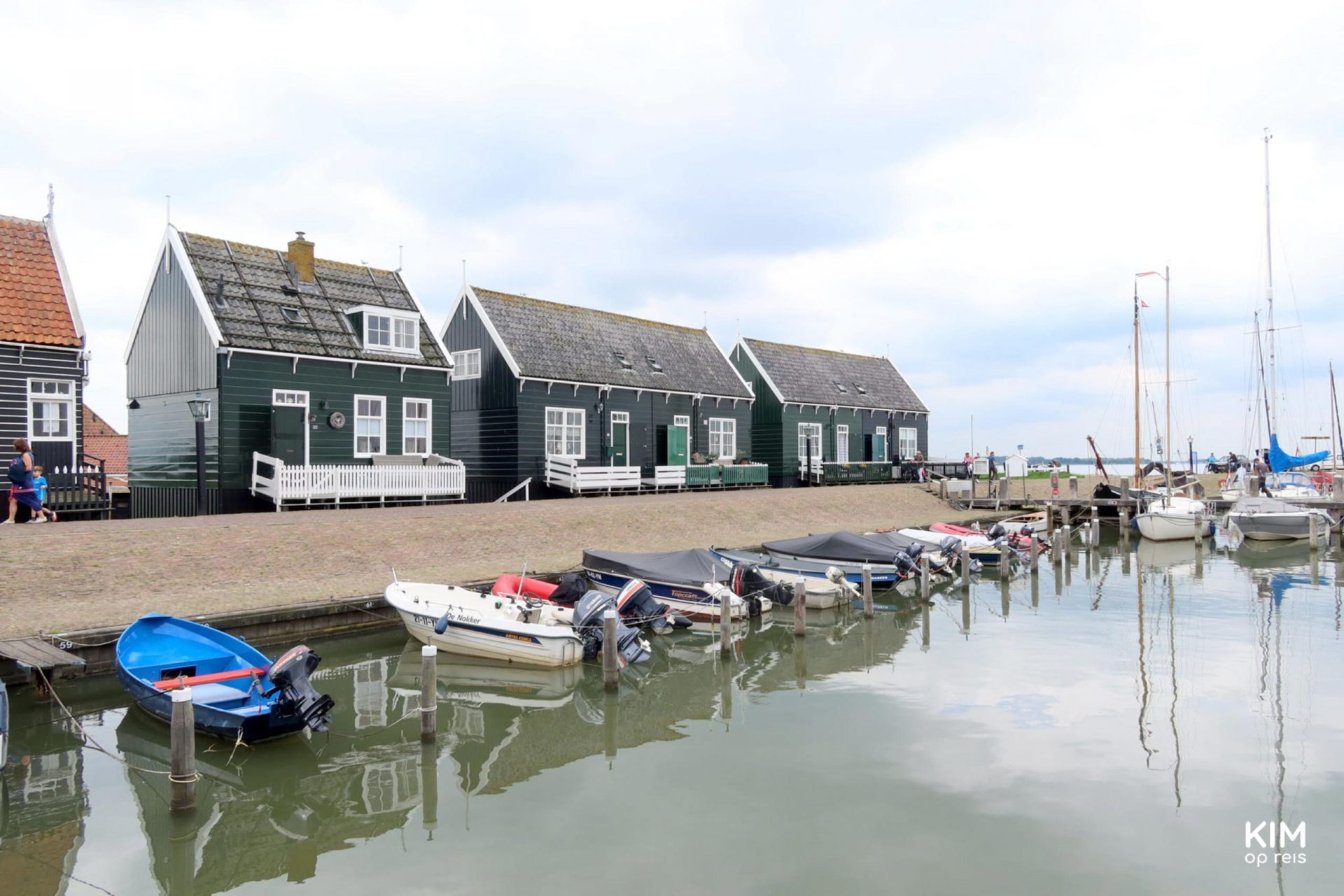 Harbor of Marken - small motorboats in the water and on the side some dark green wooden Marker houses