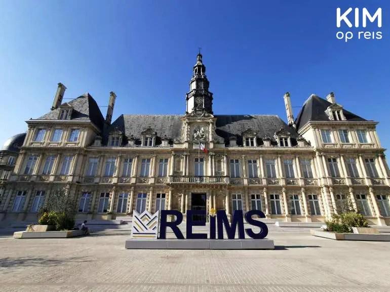 """Hôtel de Ville Reims: het stadshuis met daarvoor in grote blauwe letters """" Reims"""""""