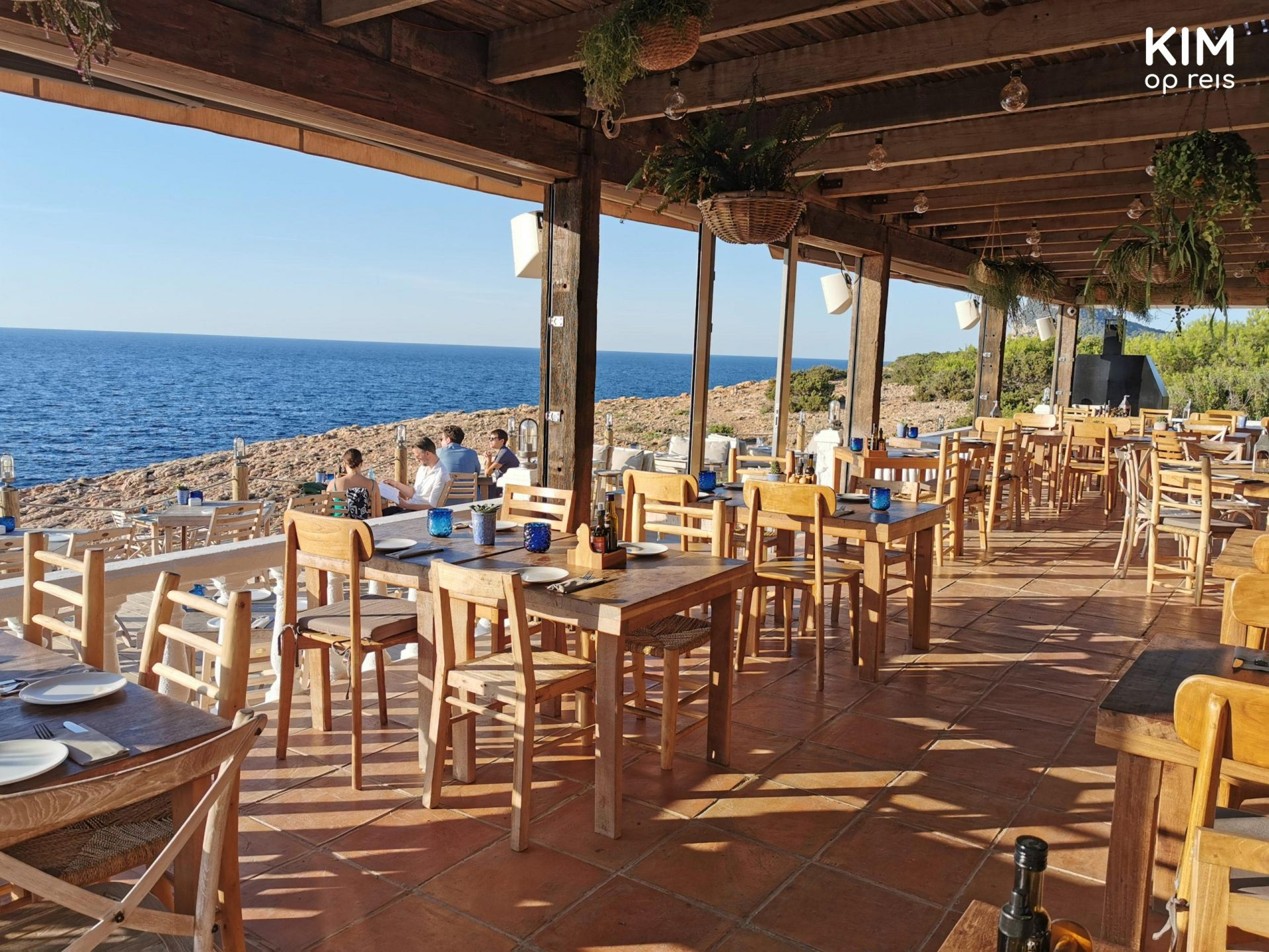 Hostal La Torre terrace - an almost empty covered terrace with simple wooden tables