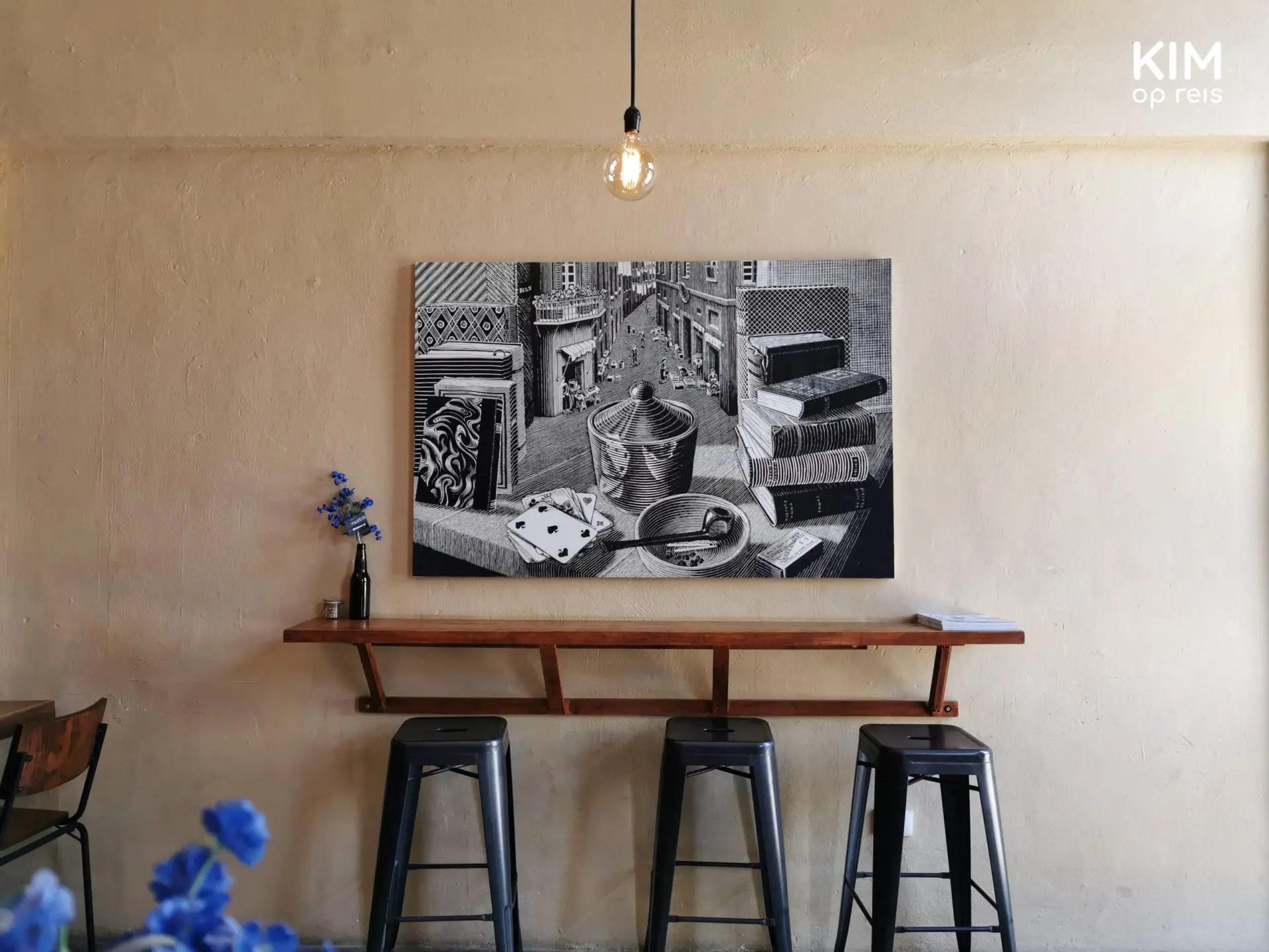 Interieur Manifesto koffiecafe: bartafel aan de muur met drie krukken en een zwart wit stilleven