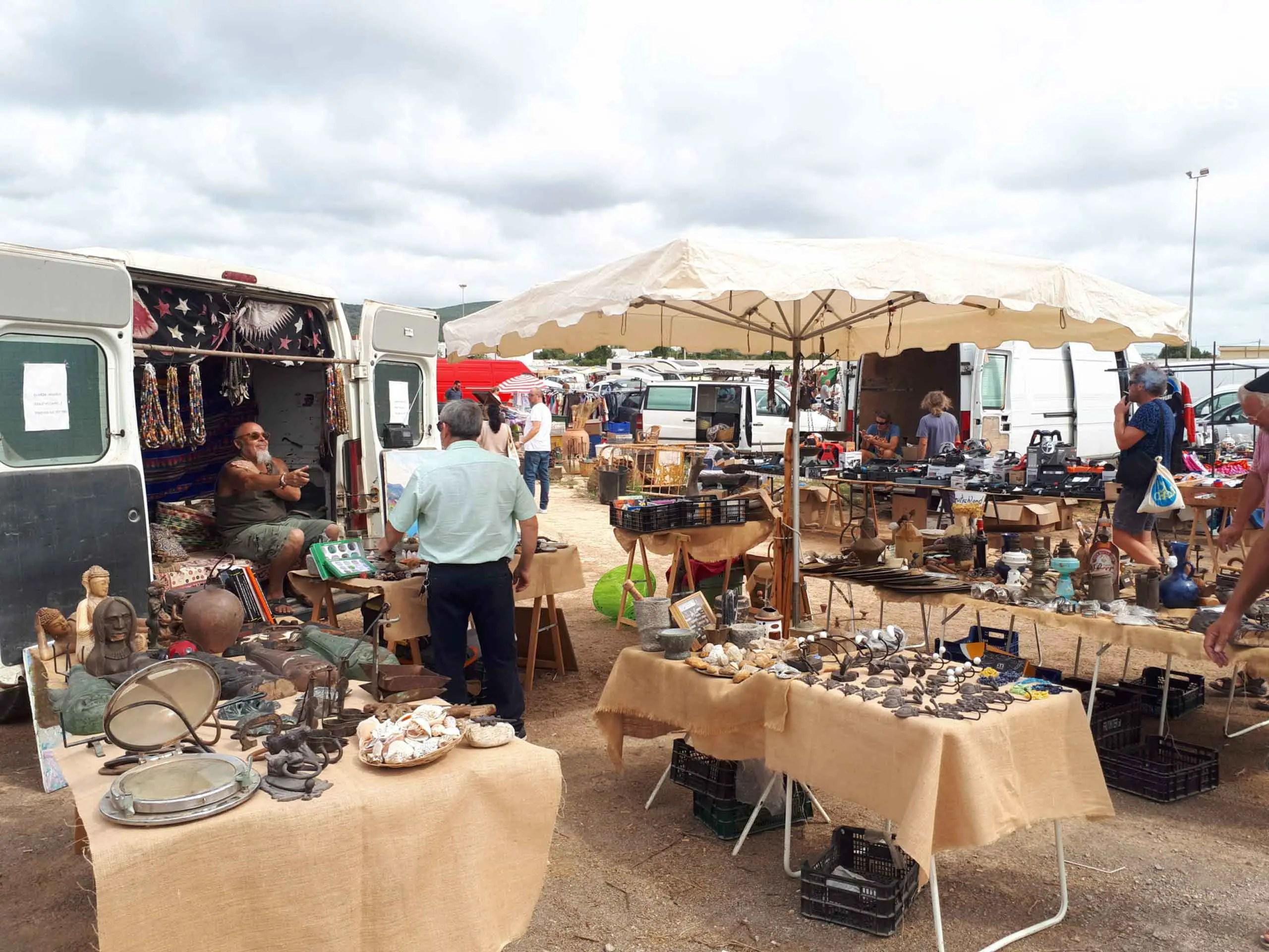 Sant Jordi markt Ibiza - Kunst en kitsch, antiek en prullaria te koop uitgestald op enkele tafels met een parasol erboven