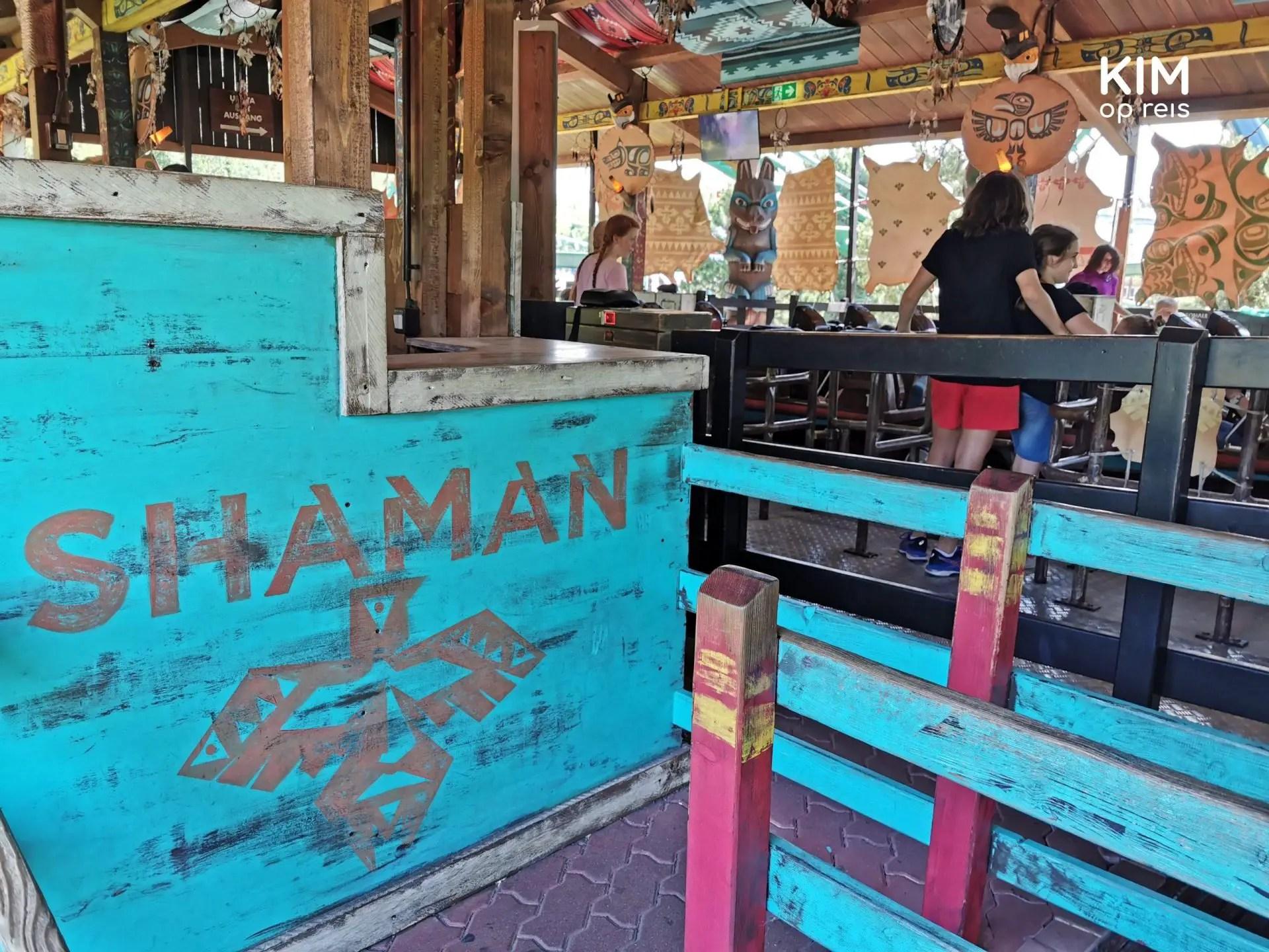 Shaman achtbaan Gardaland - logo van de Shaman attractie op een blauwgekleurd schot met op de achtergrond de achtbaan