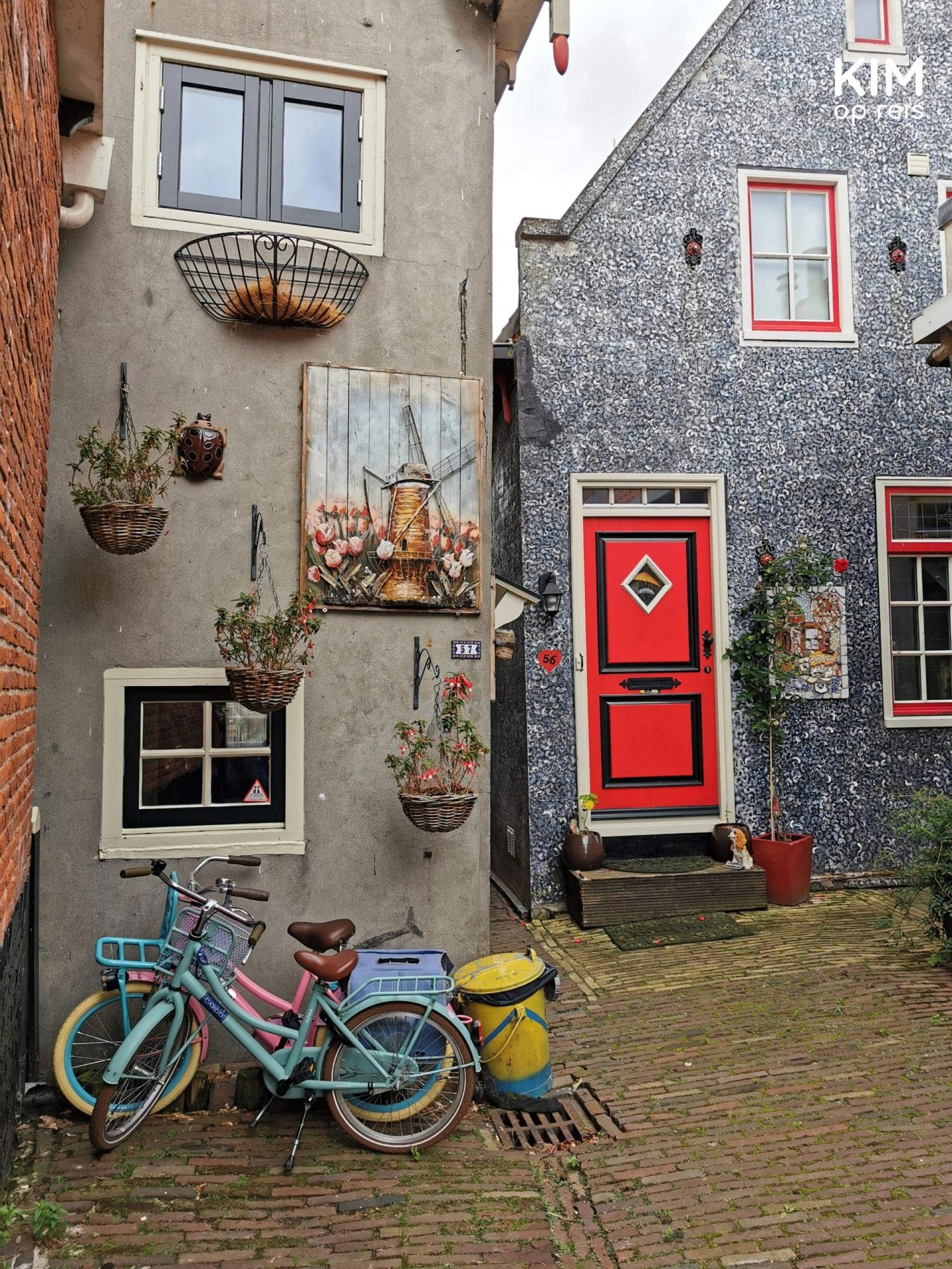 Volendam visit the Doolhof - View through to a gray-colored house with red details, hanging flower pots, and two small bicycles in front