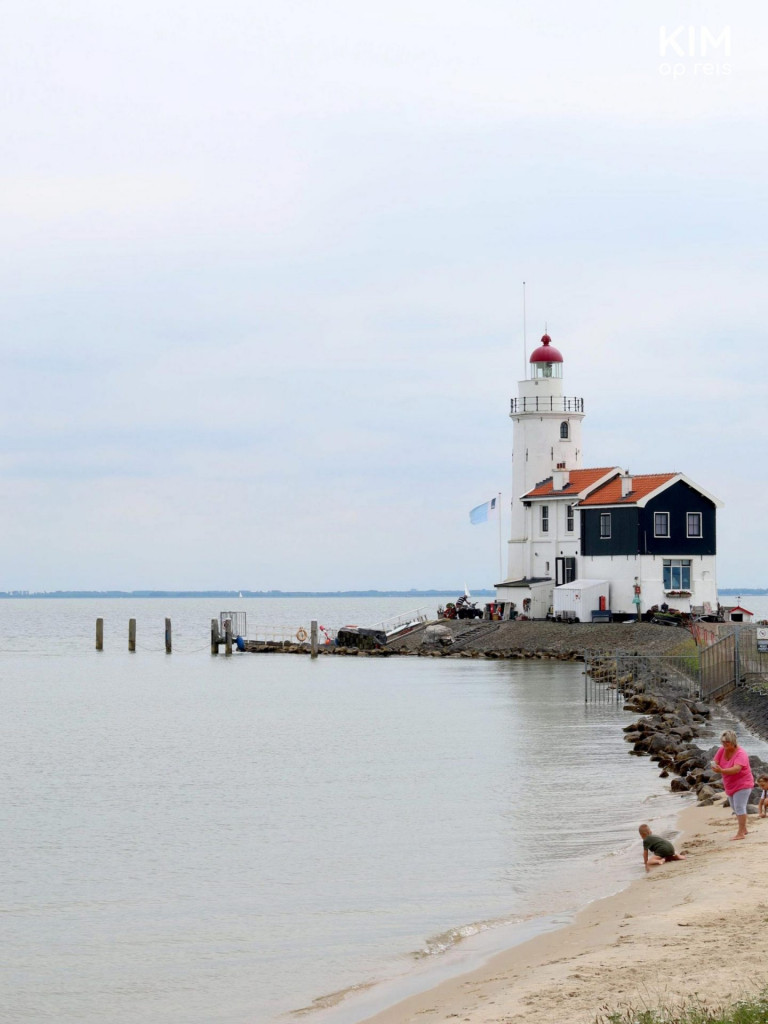 Lighthouse Marken Paard van Marken - White lighthouse with a white and dark-colored house on the dike