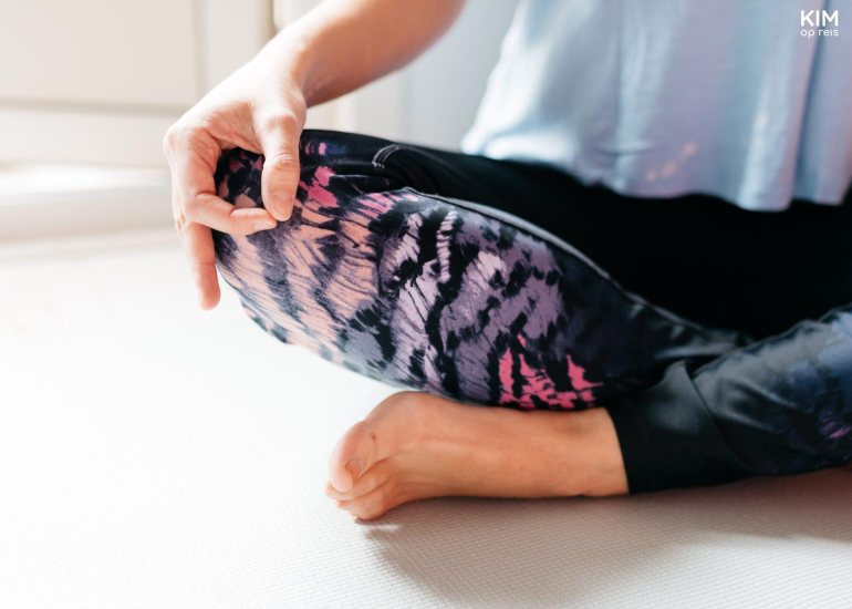 Yoga weekend belgie: closeup van een vrouw die zit met haar hand in meditatiepose op haar knie