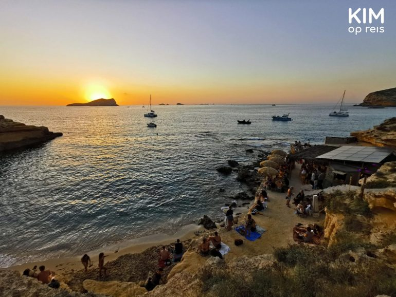 Sunset Ibiza Cala Comte: view over the rocky beach with spectators of the sunset