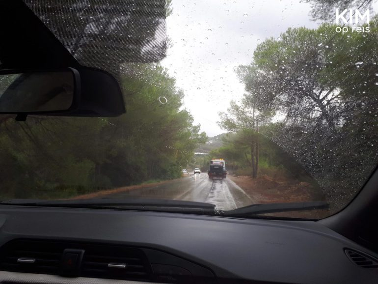 Regen op Ibiza, droog in de auto - regen en natte autoweg door een autoraam gezien