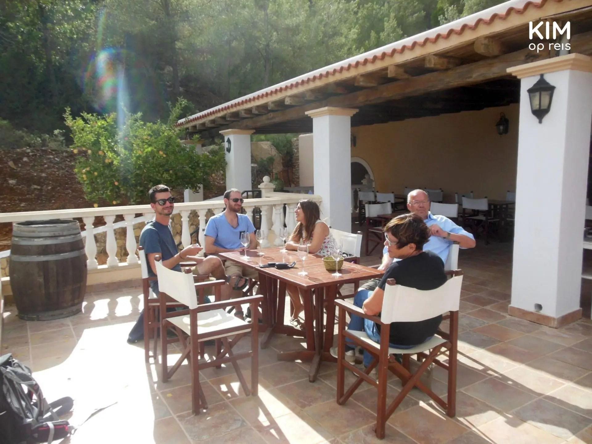 Wijnproeverij op het terras bij Sa Cova - vijftal zit aan tafel met wijnglazen