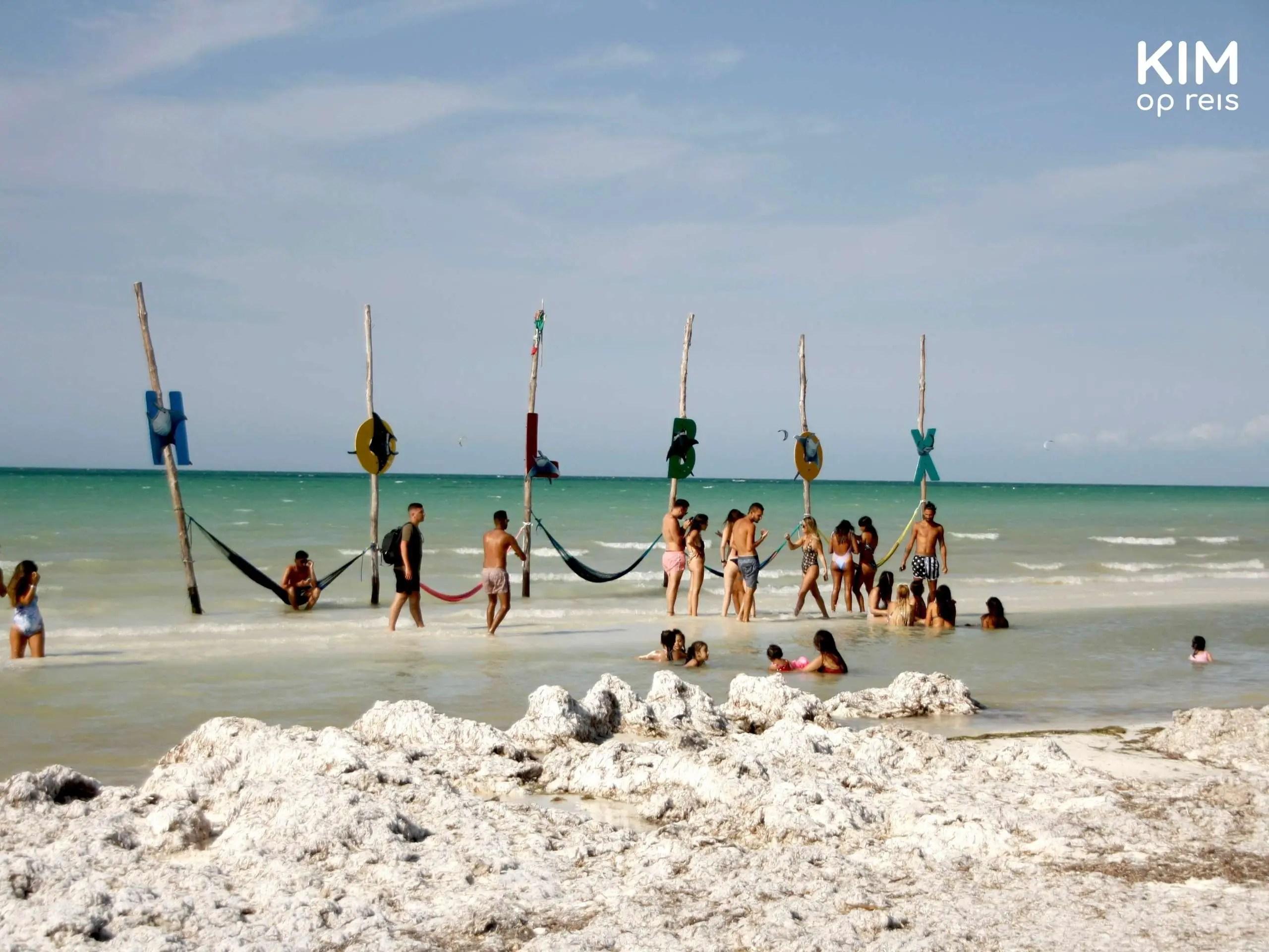 Isla Holbox strand hangmat zee: strand met mensen en hangmatten in de zee