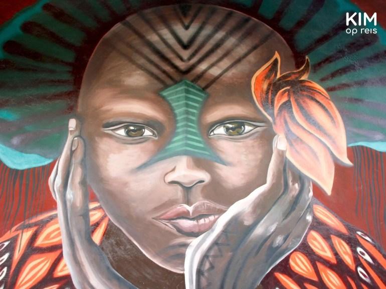 Isla Holbox street art meisje bloem: muurschildering van donker meisje