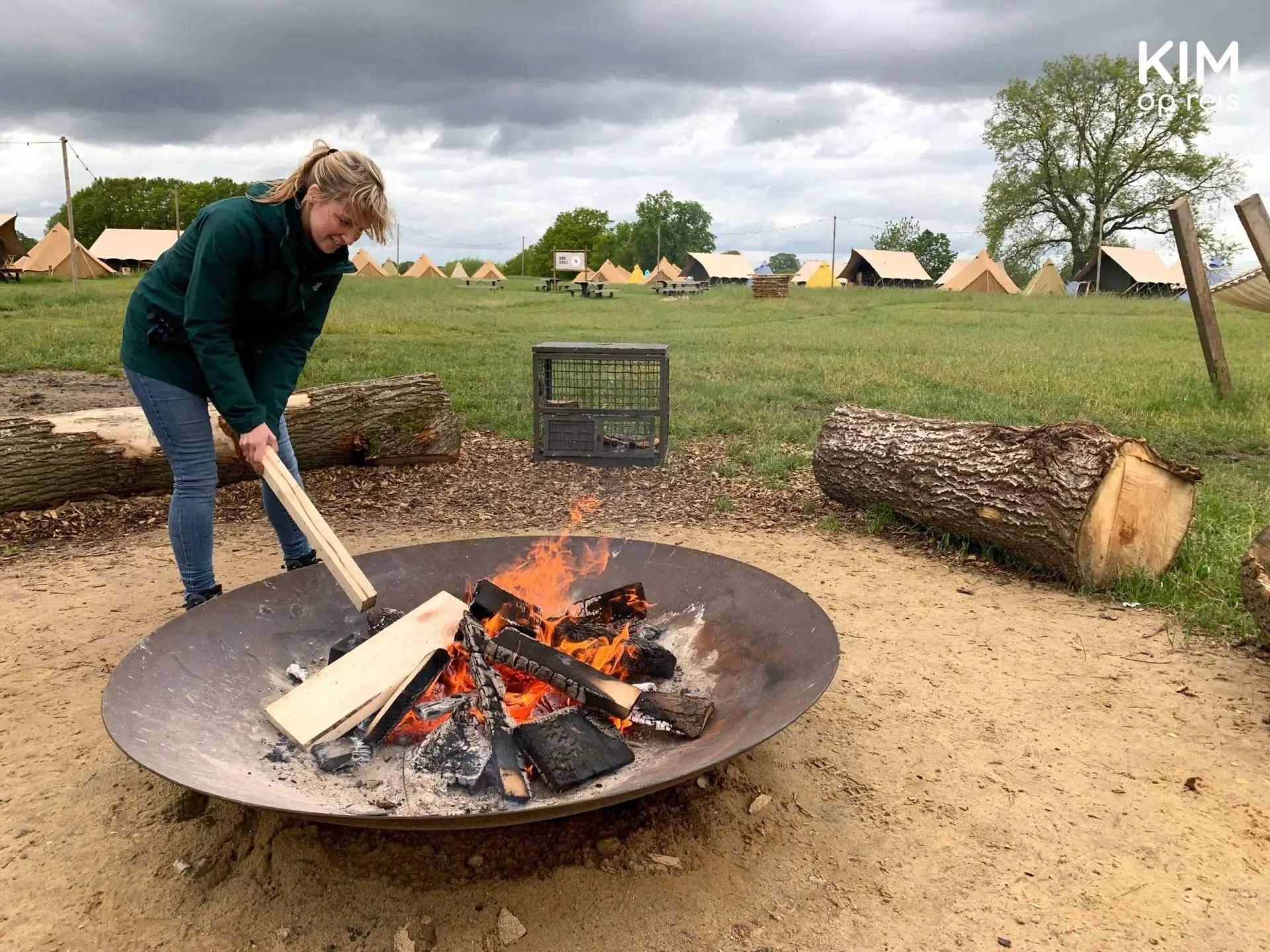 kampvuur Bij de Buren Mölke Zuna: Kim port met een stuk hout in de vuurschaal