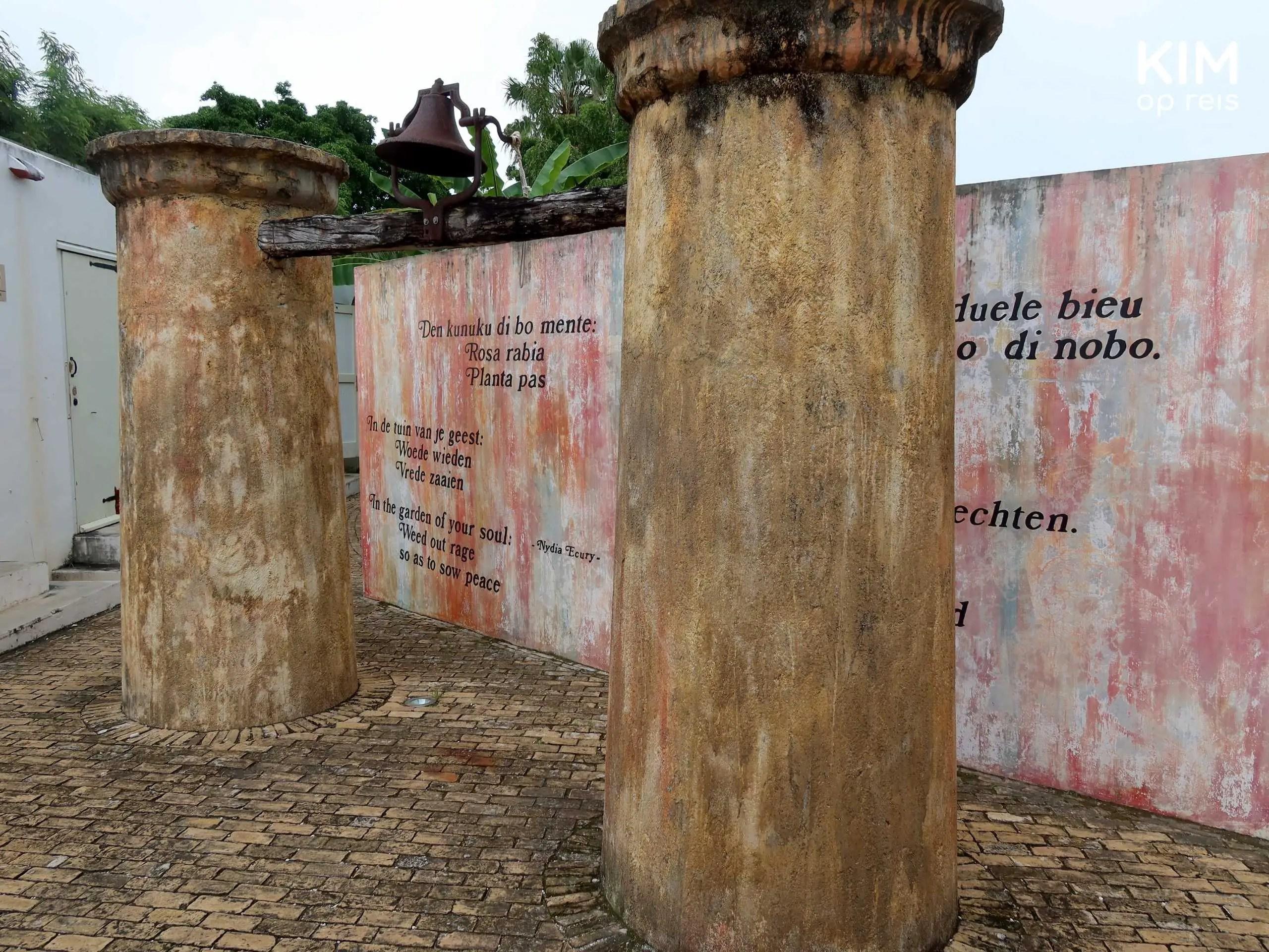 Kura Hulanda museum Willemstad: twee pilaren met op de achtergrond een muur met in verschillende talen: In de tuin van je geest: woede wieden, vrede zaaien