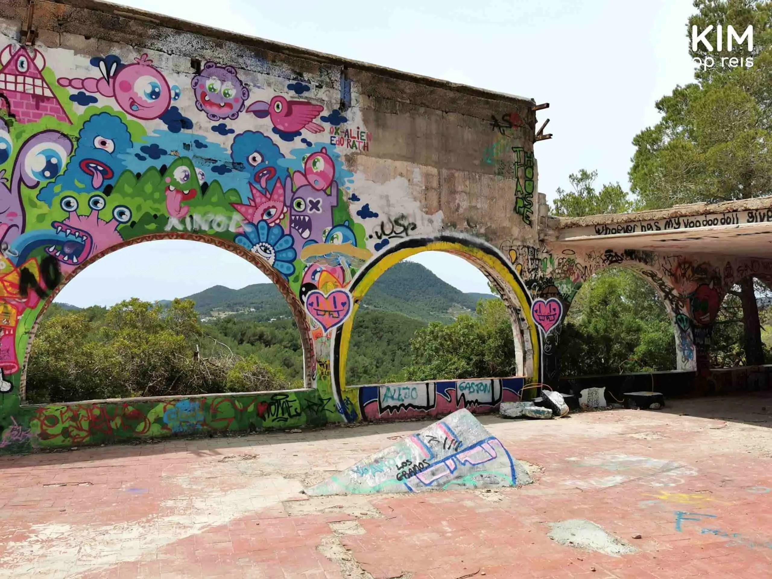 Abandoned Festival Club natuur: hoge muur met bogen onderin die uitzicht geven op het amfitheater