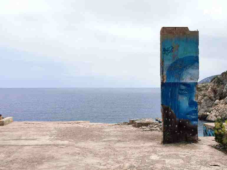 Graffiti sea Ibiza: concrete plateau by the sea with a piece of wall with a blue painting of a head