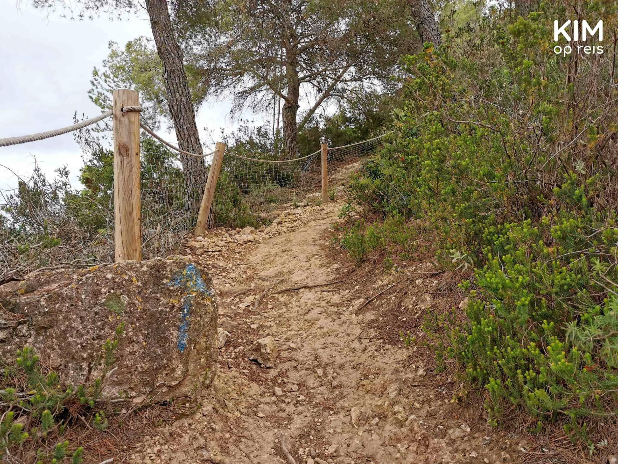 wandelpad Sa Talaia: steil stuk wandelpad met op een steen een blauwe pijl omhoog geschilderd