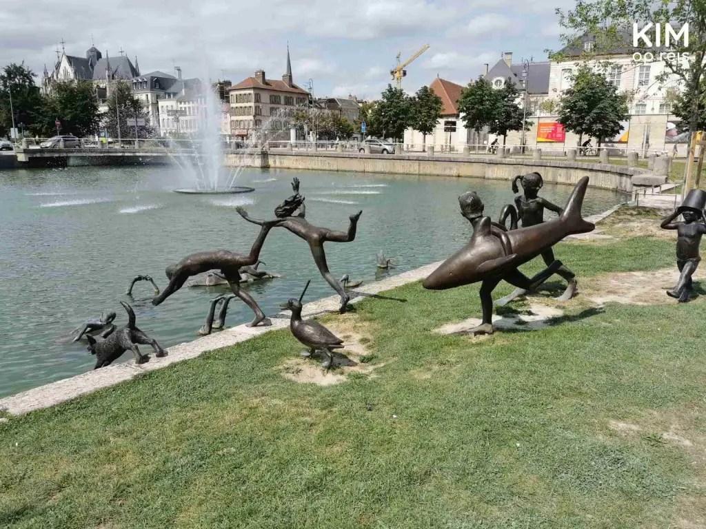 Beelden spelende kinderen dieren Troyes: groepje rent en springt richting het water