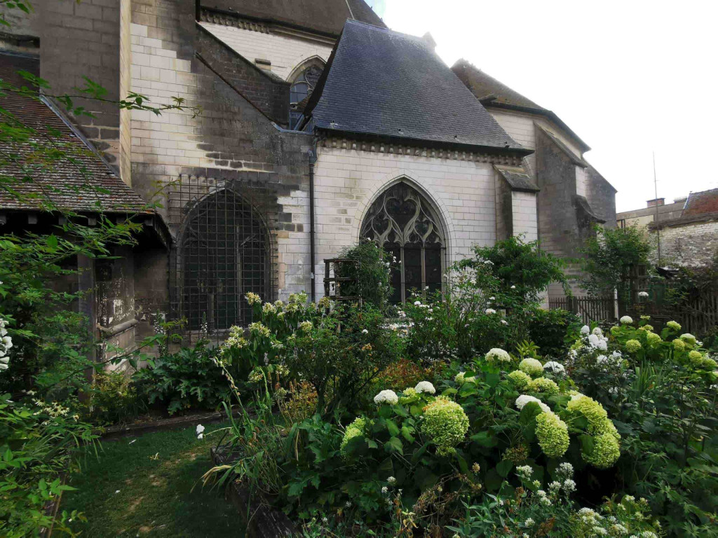 Tuin kerk jardin des innocentes: dichtbegroeide tuin naast een kerk