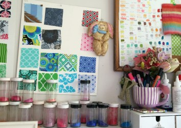 Fabric samples and crushed pastels in jars