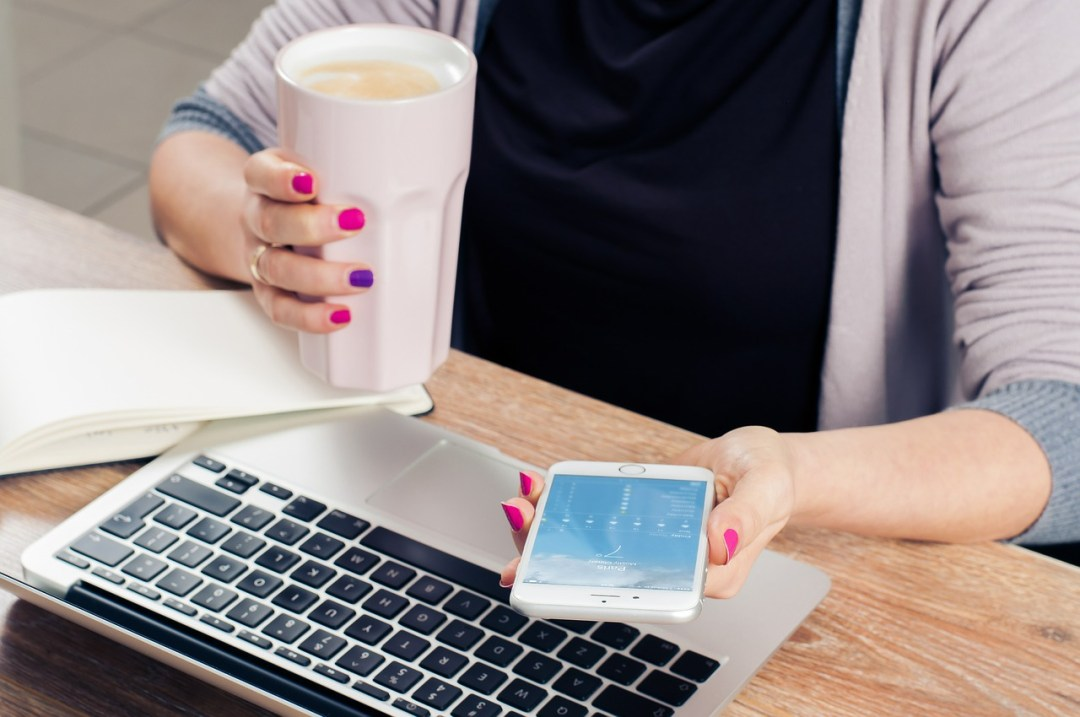 woman working at computer with cell phone