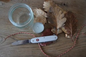 Alles was Ihr für ein Windlicht braucht: Taschenmesser (Schweizer), Teelicht, Laub, eine Schnur/Band und ein leeres Glas. Foto (c) kinderoutdoor.de