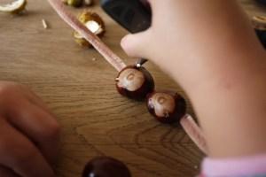 Beim Basteln fädeln die Kinder die beiden großen Kastanien auf den Pfeifenputzer auf. foto (c) kinderoutdoor.de
