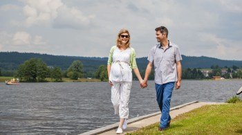 Schwangeres Paar beim Spaziergang - Rückenorthese in der Schwangerschaft