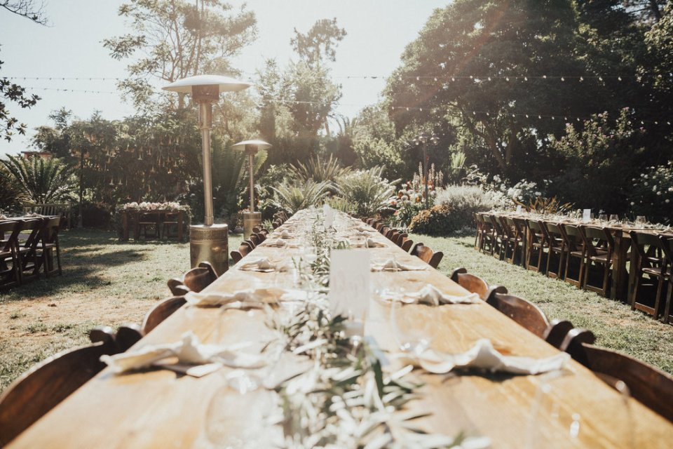 Long wood tables with minimalist napkins and biodegradable silverware for intimate wedding