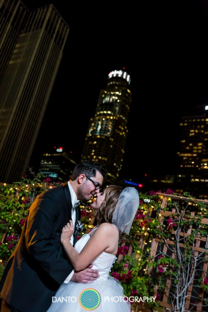 Bride and Groom kiss on Los Angeles rooftop with skyline at night