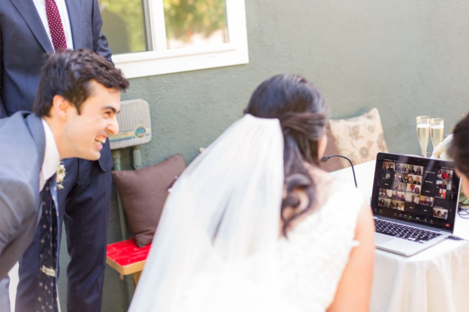 Bride and Groom watch guests toast virtually during wedding livestream
