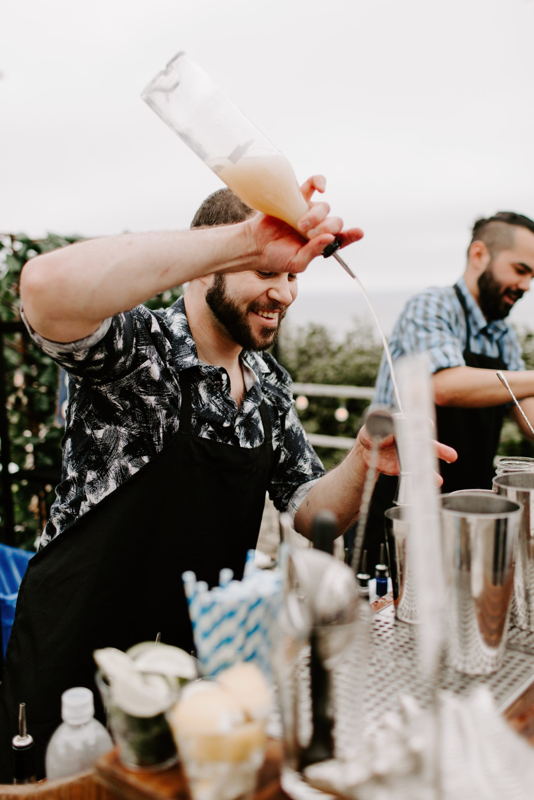 Bartender pours drinks at outdoor wedding