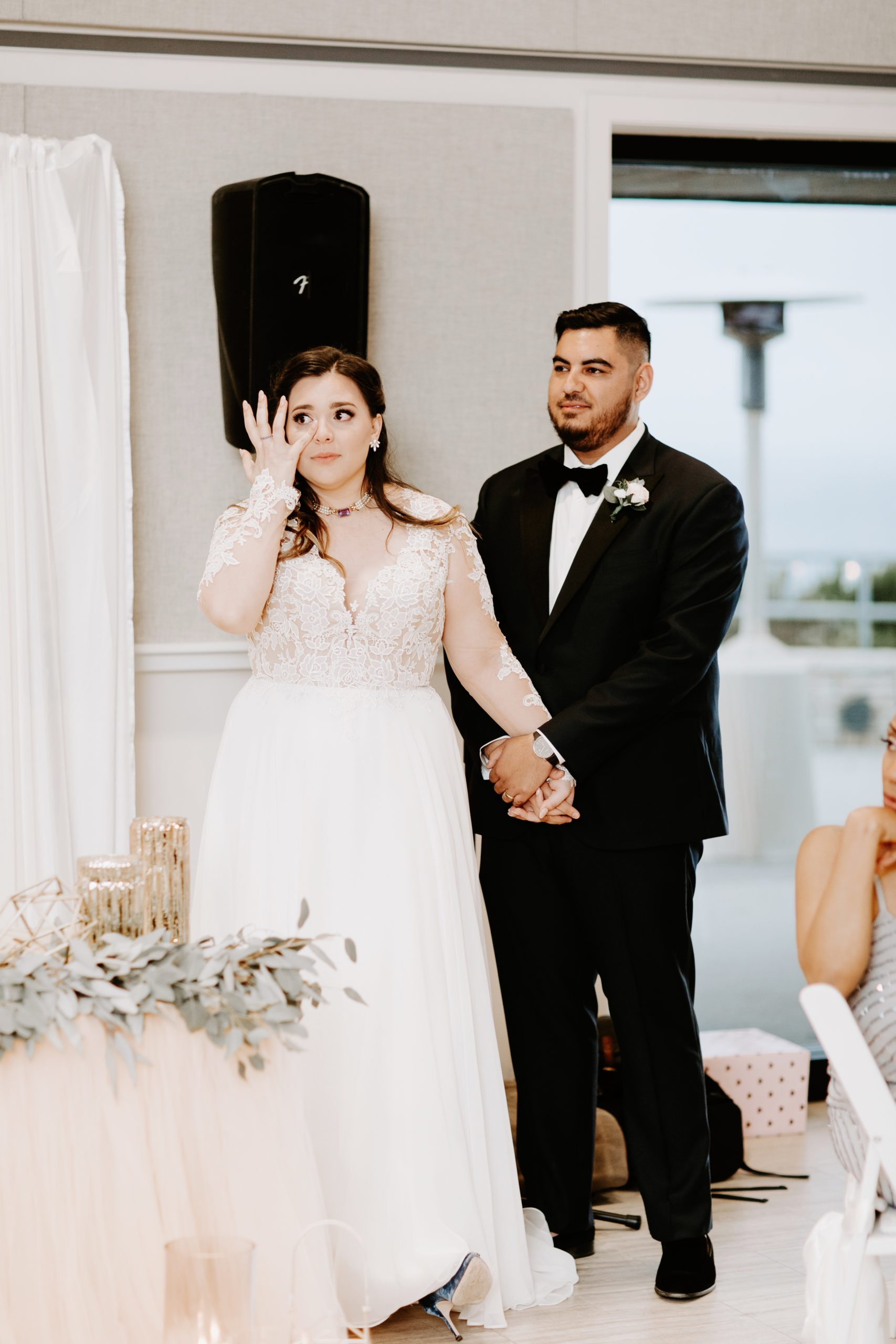 Emotional bride and groom listen to wedding toasts