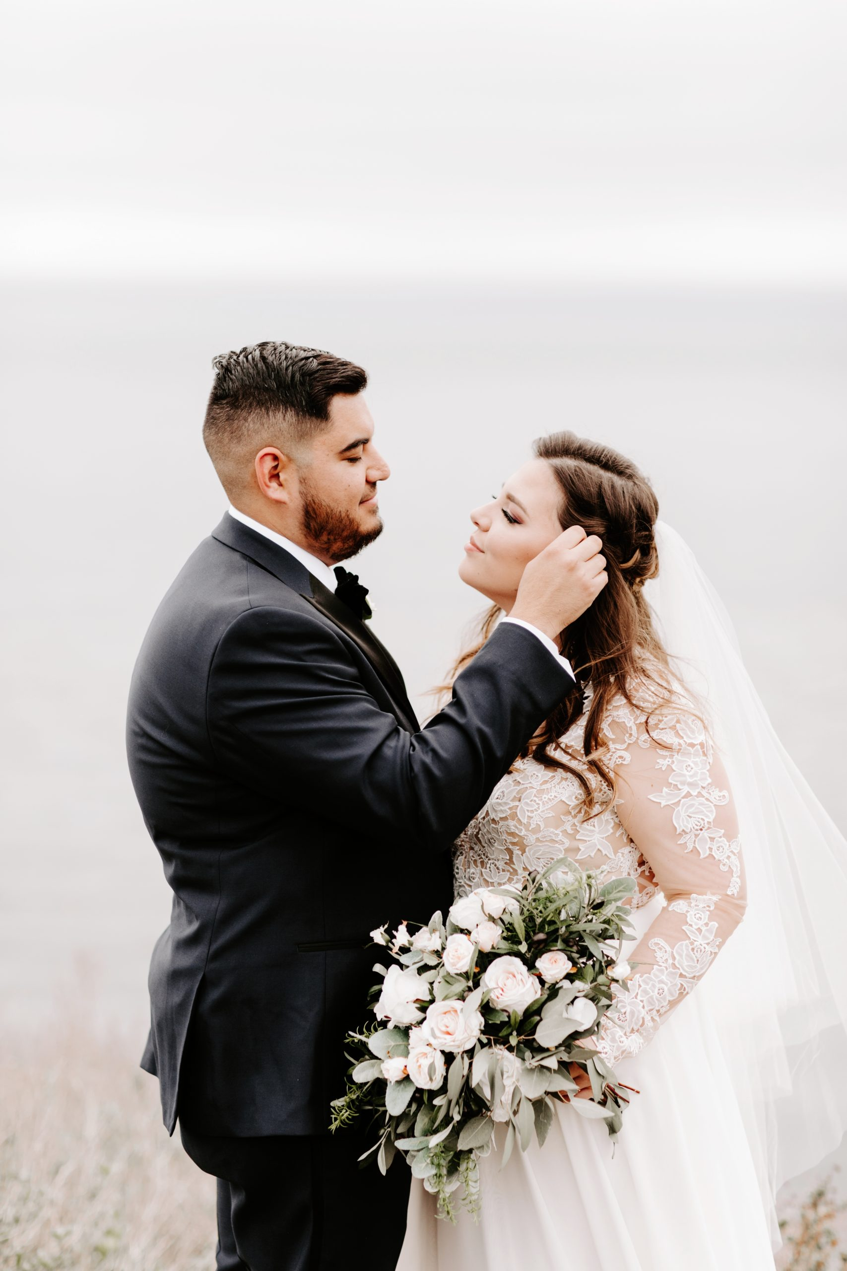 Groom brushes hair from brides face romantically
