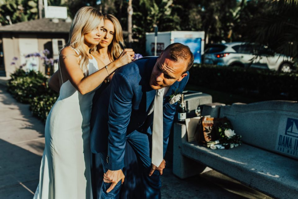 Bride signs marriage license using groom's back as table