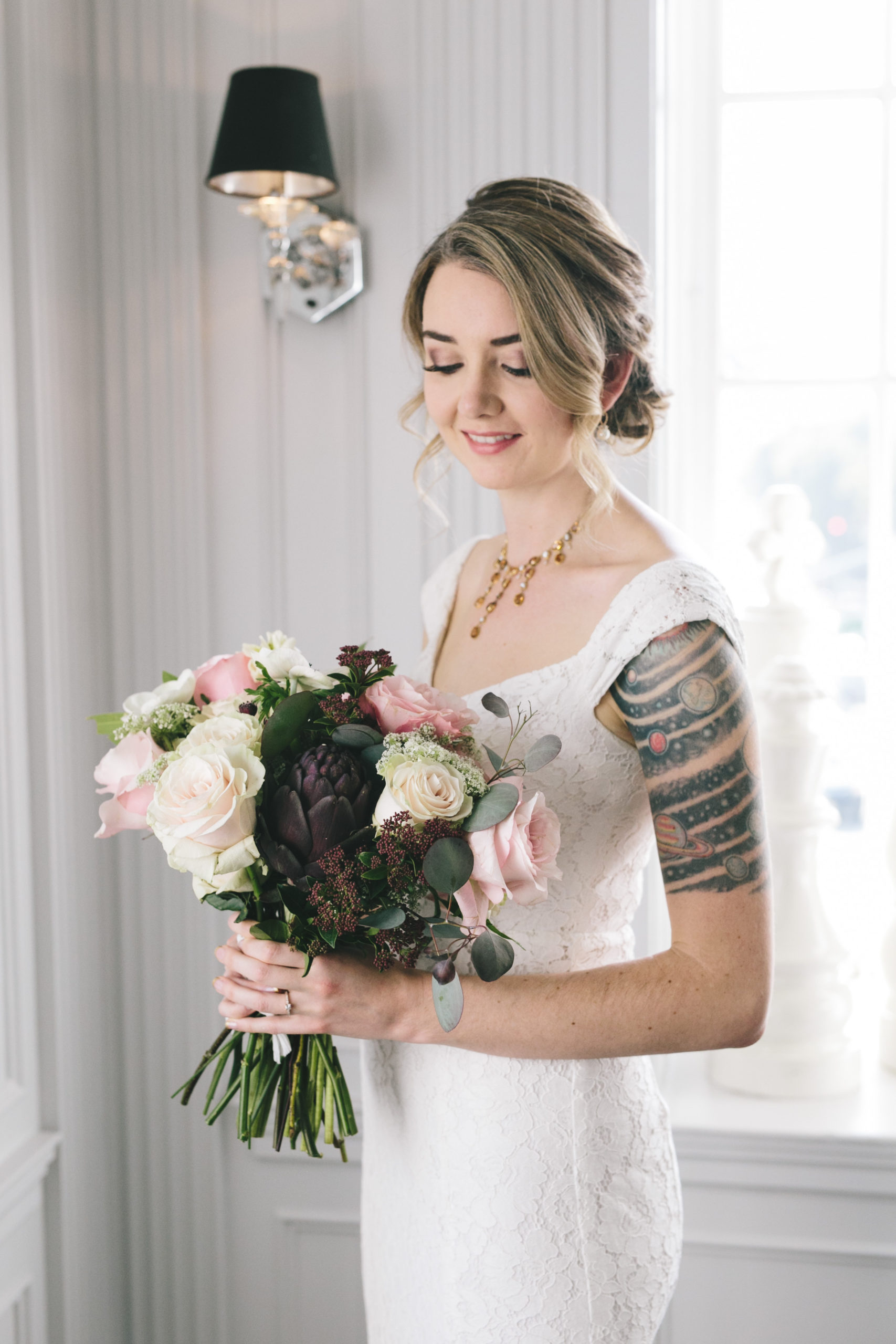 Bride with tattoo holding bridal bouquet