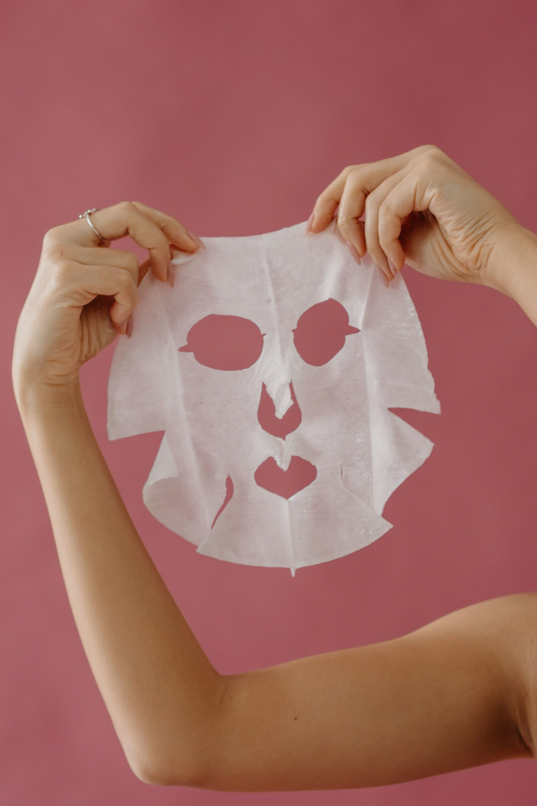 person holding up face mask