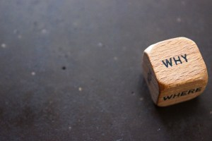 Wooden dice with the word Why on top of it