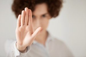 Close up isolated shot of woman with short brunette hair making stop gesture with her hand. Female entrepreneur showing stop sign, not wanting to continue business talks. Selective focus on the hand