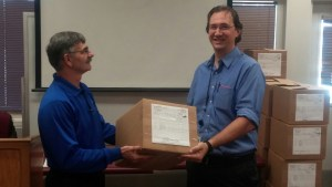 Photo of Metro instructor handing student box of gear and certificate of completion.