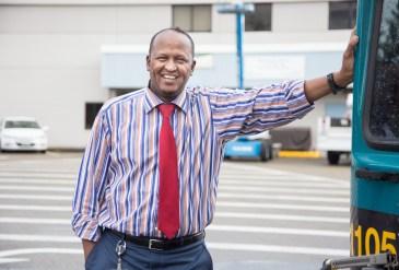 Photo of Abdi Elmi, Metro base chief, standing next to a Metro bus