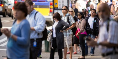 Riders wait at a downtown bus stop in Seattle