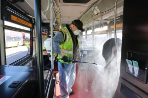Larry Bowles, Equipment service worker for King County Metro sprays the interior of a Metro bus with Virex II 286 disinfectant with a wand and backpack sprayer.