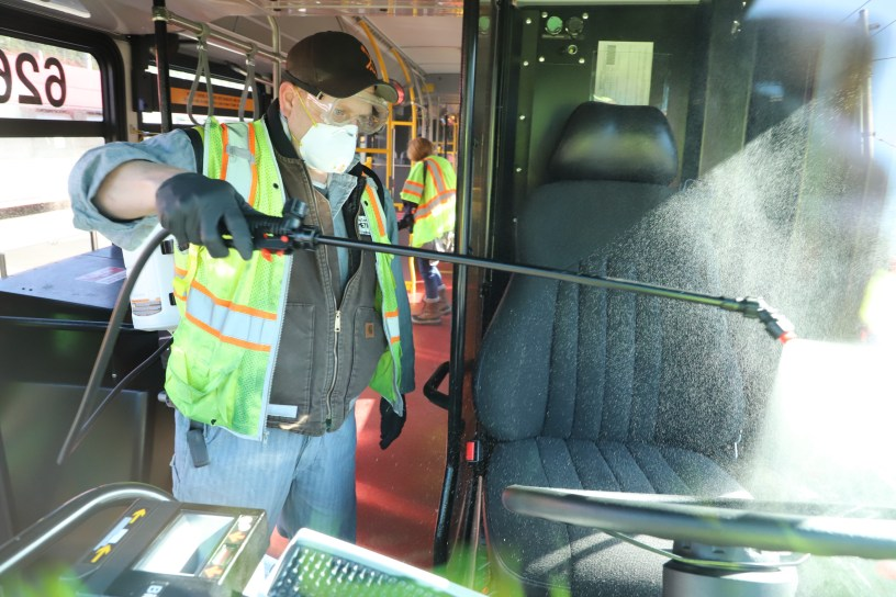 Larry Bowles Equipment Service worker for King County Metro sprays Virex II 286 on a transit operator's works space, seat and controls using a wand and backpack sprayer.