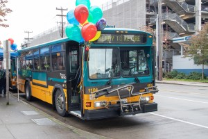 "1100 model bus being retired appears on streetside with balloons and ""Ready to Retire"" across reader board"
