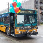 """1100 model bus being retired appears on streetside with balloons and """"Ready to Retire"""" across reader board"""