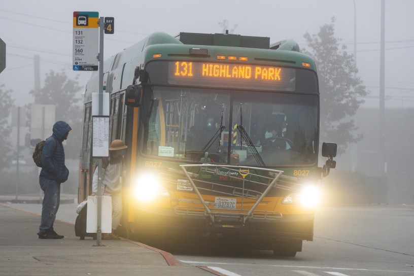 Rider boards a route 131 bus in a fog-shrouded scene in October 2020