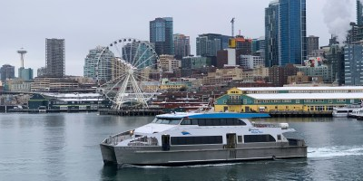 Doc Maynard headed for West Seattle from downtown Seattle with city Skyline in the background