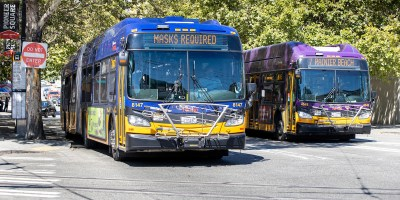 two buses in downtown Seattle, one reads Masks Required
