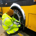 Vehicle Maintenance chaining up a bus during snow